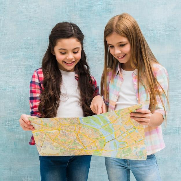 Zwei nette mädchen, die gegen die blaue gemalte wand stehen, die in der karte sucht Kostenlose Fotos