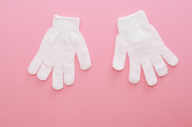 Zwei peeling-massage-handschuh für die dusche auf rosa hintergrund. handschuhe für den einsatz in der dusche für massage und peeling. Premium Fotos