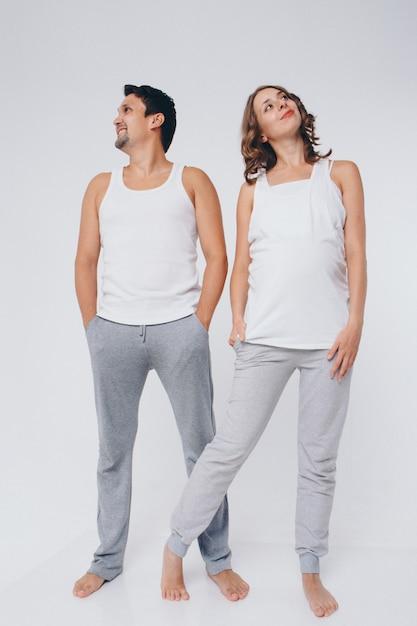 Zwei personen in identischen posen. ein mann und eine schwangere frau sehen ganz anders aus. das konzept der gesunden verdauung, lebensstil Premium Fotos