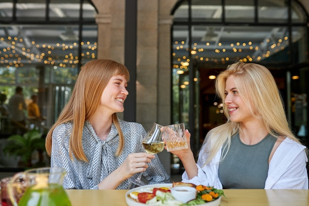 Zwei positive kaukasische frauen verbringen gerne zeit miteinander im restaurant Premium Fotos