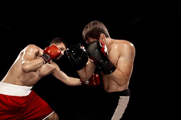 Zwei professionelle boxerboxen an der schwarzen wand Kostenlose Fotos