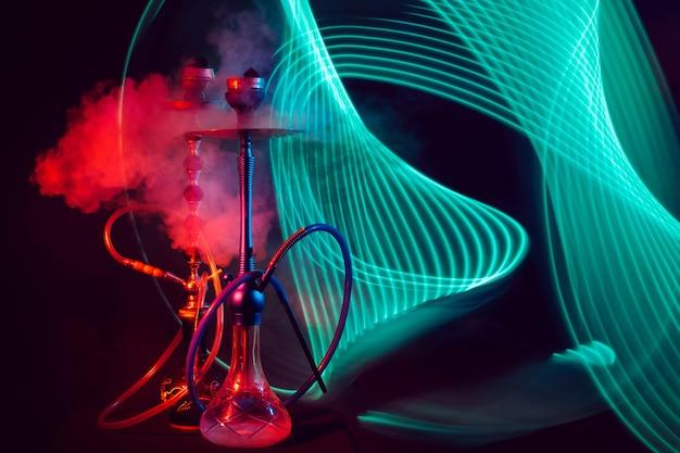 Zwei rauchige wasserpfeifen mit glasflaschen wasser mit shisha-kohlen mit rotgrüner neonbeleuchtung auf einem schwarzen hintergrund Premium Fotos