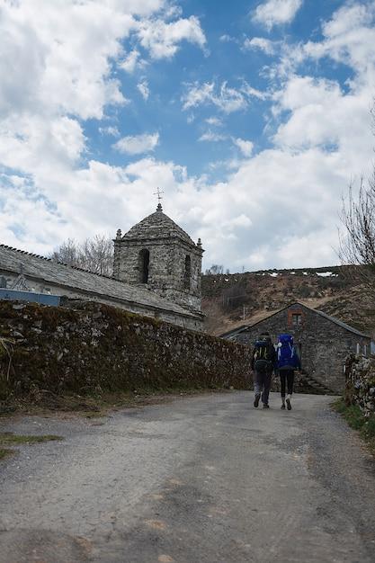 Zwei reisende gehen an der alten kapelle vorbei auf dem weg nach santiago de compostela Premium Fotos