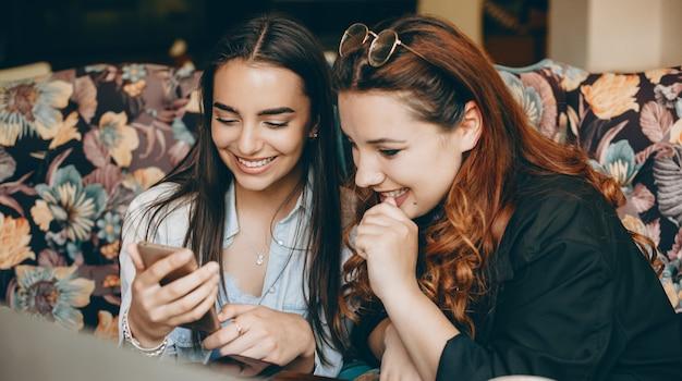 Zwei reizende junge frau, die einen smartphone-bildschirm lachend betrachtet, während sie in einem café sitzt. Premium Fotos