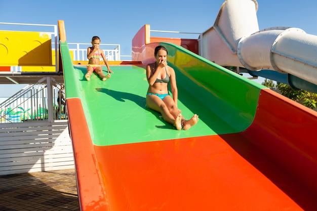 Zwei reizende süße lustige schwestern steigen von einer bunten hellen rutsche in einen pool mit klarem transparentem wasser ab und genießen die warme helle sonne Premium Fotos