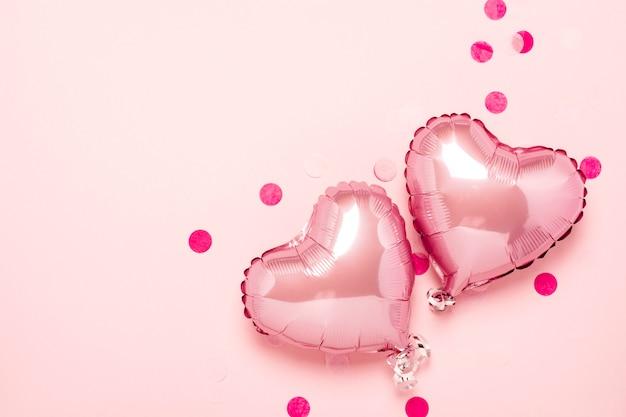 Zwei rosa luftballons in form eines herzens auf einem rosa hintergrund. valentinstag, hochzeitsdekoration. folienkugeln. flachgelegt, draufsicht Premium Fotos