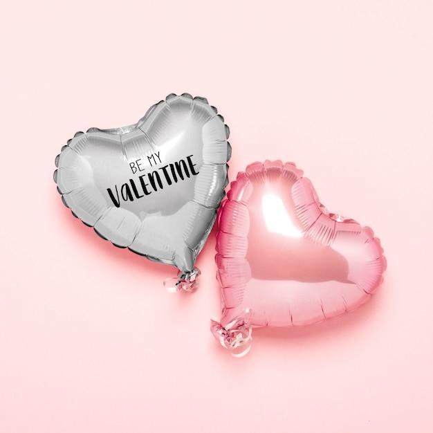 Zwei rosa luftballons in form eines herzens auf einer rosa oberfläche. konzept valentinstag Premium Fotos