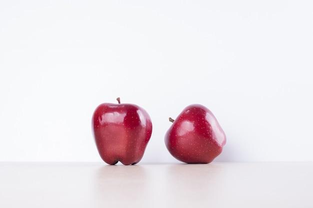 Zwei rote äpfel auf weißer oberfläche. Kostenlose Fotos