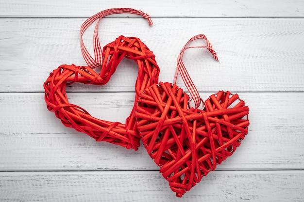 Zwei rote hausgemachte herzen mit band auf weißem hölzernem hintergrund. symbol der liebe, romantischer hintergrund. festliche geschenkkarte am valentinstag. Premium Fotos