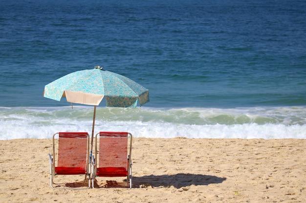 Zwei rote strandstühle und blauer sonnenschirm auf copacabana setzen, rio de janeiro, brasilien auf den strand Premium Fotos