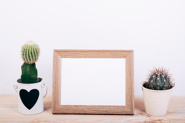 Zwei saftige anlagen auf seiten des leeren fotorahmens auf hölzernem schreibtisch Kostenlose Fotos