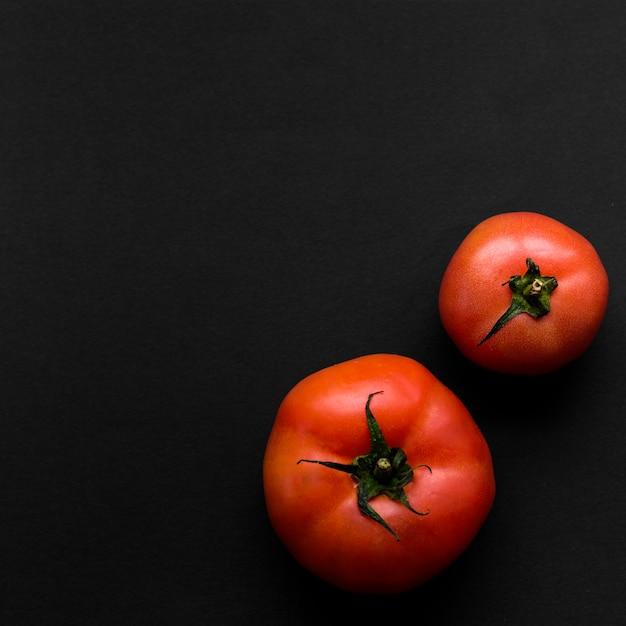 Zwei saftige rote tomaten auf schwarzem hintergrund Kostenlose Fotos