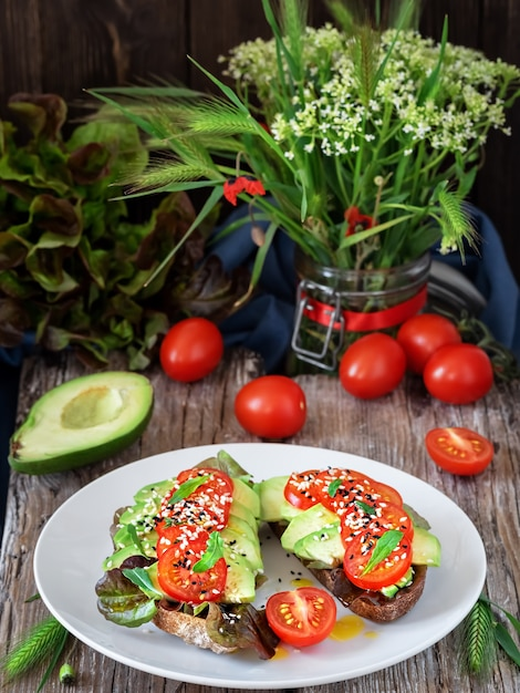 Zwei sandwiches mit frisch gebackenem brot, olivenöl, salat, avocado, sesam und kirschtomaten auf einem weißen teller Kostenlose Fotos
