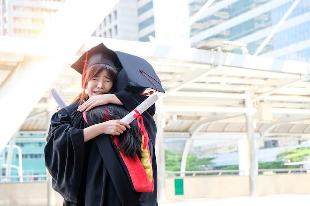 Zwei schöne asiatische mädchen umarmen die abschlusszeremonie Premium Fotos