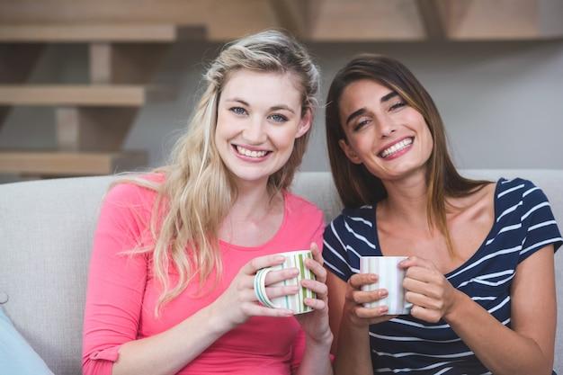 Zwei schöne frauen, die nebeneinander mit einem becher kaffee sitzen Premium Fotos