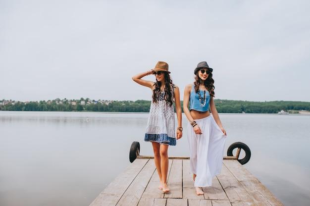 Zwei schöne freundinnen auf dem dock Premium Fotos