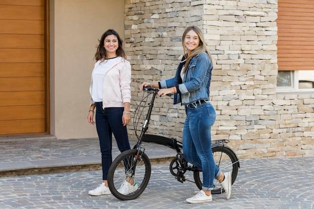 Zwei schöne freundinnen, die außerhalb des hauses mit fahrrad gehen Kostenlose Fotos