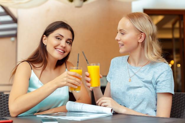 Zwei schöne junge mädchen, die durch die tabelle im café sitzen Premium Fotos