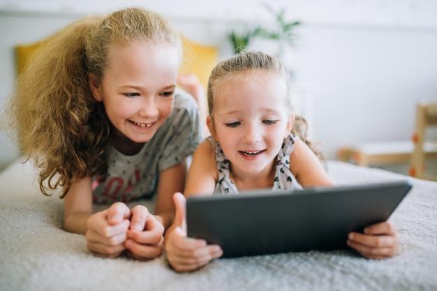 Zwei schöne kleine schwestern, die im bett liegen und den schirm einer tablette, intelligente kinder unter verwendung der intelligenten technologie betrachten Premium Fotos