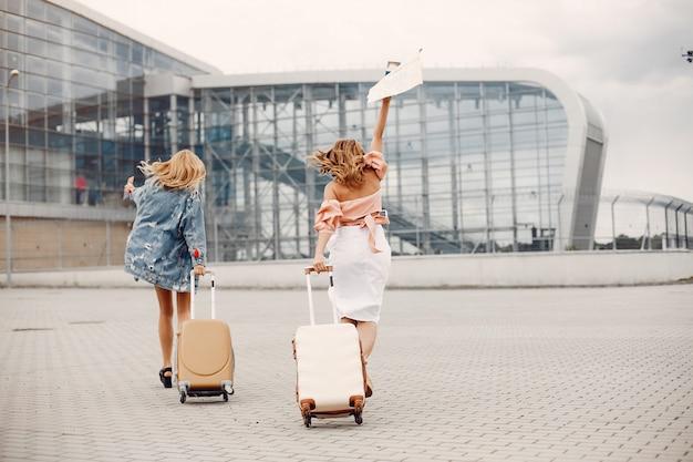Zwei schöne mädchen, die den flughafen bereitstehen Kostenlose Fotos