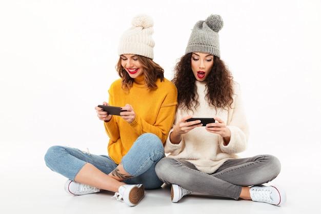 Zwei schöne mädchen in den strickjacken und in hüten, die zusammen auf dem boden bei der anwendung ihrer smartphones über weißer wand sitzen Kostenlose Fotos
