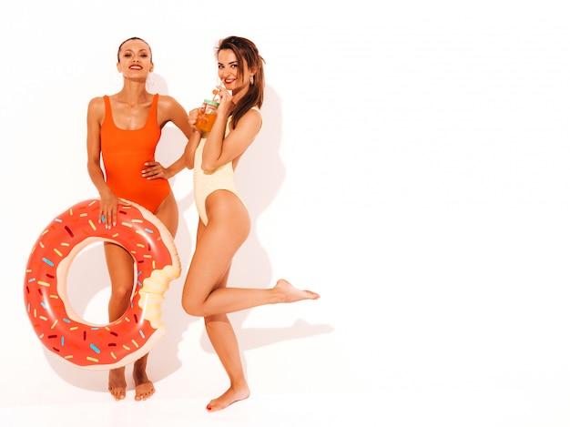 Zwei schöne sexy lächelnde frauen in den bunten badebekleidungsbadeanzügen des sommers. mädchen isoliert. lustige modelle, die neues cocktail smoozy getränk mit aufblasbarer matratze des donuts lilo trinken Kostenlose Fotos
