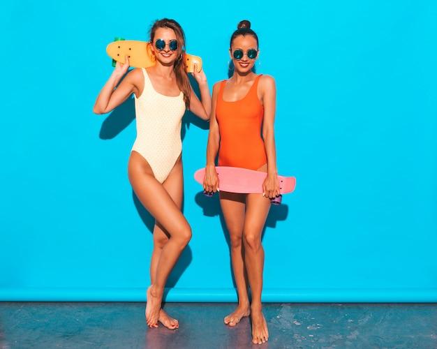 Zwei schöne sexy lächelnde frauen in den bunten badebekleidungsbadeanzügen des sommers. trendy girls in sonnenbrillen. positive modelle, die spaß mit bunten penny-skateboards haben. isoliert Kostenlose Fotos