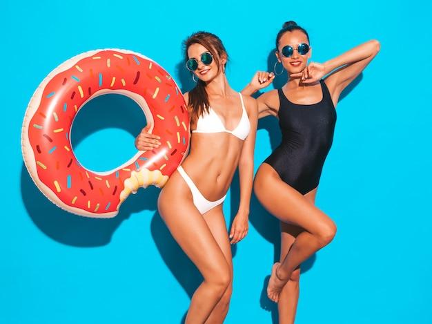 Zwei schöne sexy lächelnde frauen in den weißen und schwarzen badebekleidungsbadeanzügen des sommers mädchen in der sonnenbrille. positive modelle, die spaß mit aufblasbarer matratze des donut lilo haben. lokalisiert auf blauer wand Kostenlose Fotos
