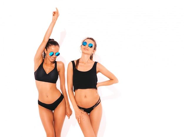 Zwei schöne sexy lächelnde frauen in der schwarzen wäsche. trendy heiße models, die spaß haben. mädchen in sonnenbrillen isoliert Kostenlose Fotos
