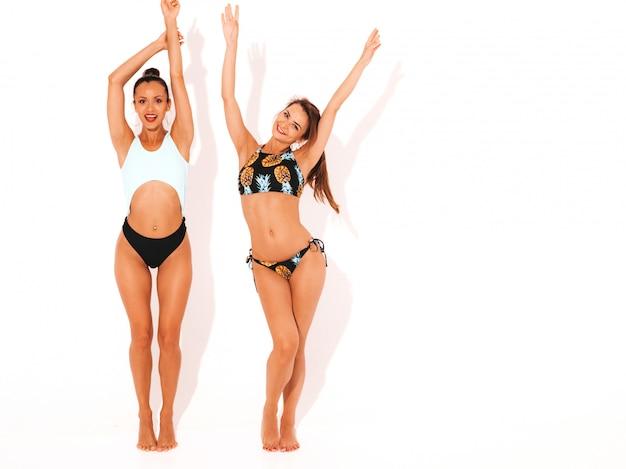 Zwei schöne sexy lächelnde frauen in der schwimmenwäsche. trendy heiße models, die spaß haben. mädchen getrennt. hände anheben, in voller länge Kostenlose Fotos