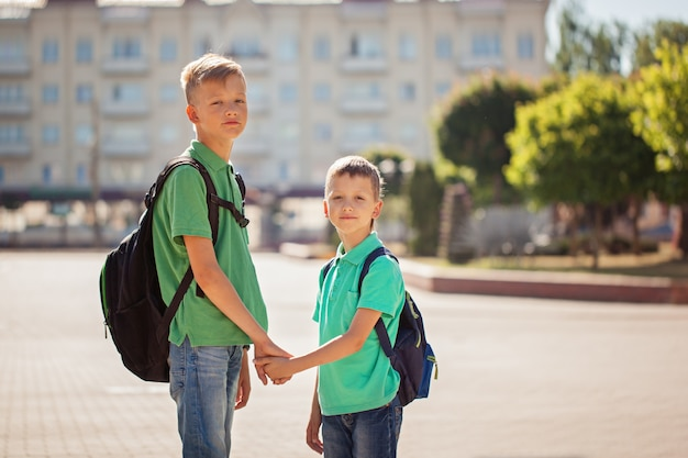 Zwei schulkinderjungen mit rucksack am sonnigen tag. glückliche kinder gehen zur schule. Premium Fotos