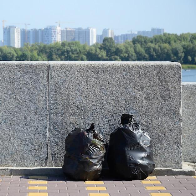 Zwei schwarze müllsäcke auf mit ziegeln gedecktem straßenboden am konkreten zaun in der stadt Premium Fotos