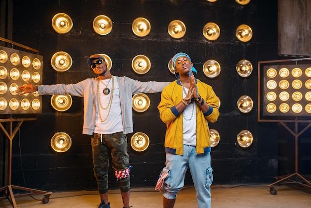 Zwei schwarze rapper in mützen, künstler posieren auf der bühne Premium Fotos
