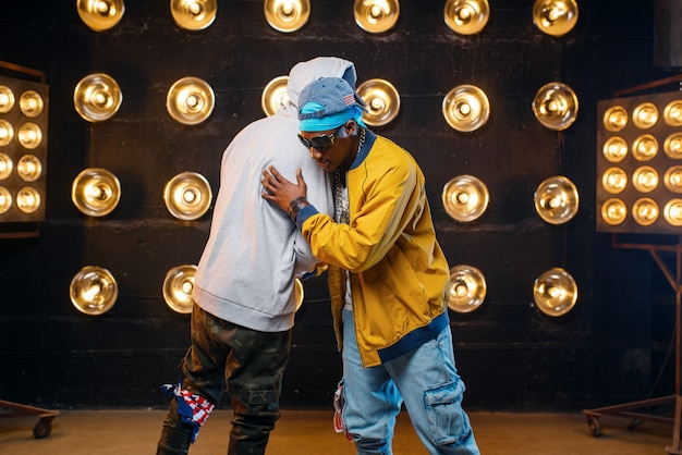 Zwei schwarze rapper in mützen umarmen sich auf der bühne, leistung im club mit scheinwerfern an der wand. rap-darsteller vor ort mit lichtern, underground-musikkonzert im urbanen stil Premium Fotos