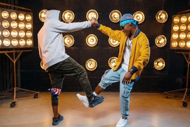 Zwei schwarze rapper in mützen umarmen sich auf der bühne Premium Fotos