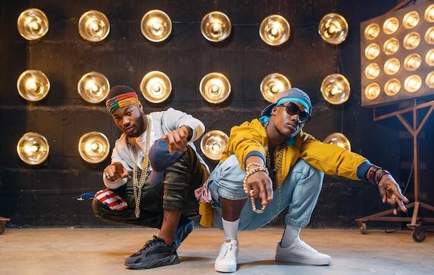 Zwei schwarze rapper sitzen auf dem boden Premium Fotos