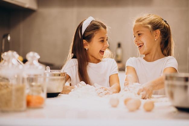 Zwei schwestern der kleinen mädchen, die an der küche kochen Kostenlose Fotos