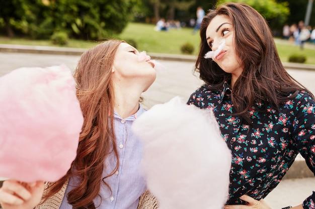 Zwei schwestern, die zuckerwatte am park essen Kostenlose Fotos