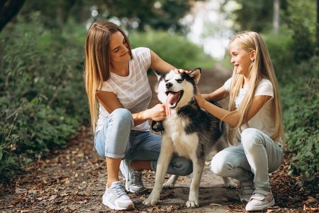 Zwei schwestern mit ihrem hund im park Kostenlose Fotos