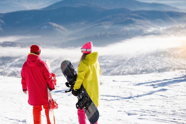 Zwei snowboarder stehen und sprechen auf dem hintergrund der blauen berge. Premium Fotos