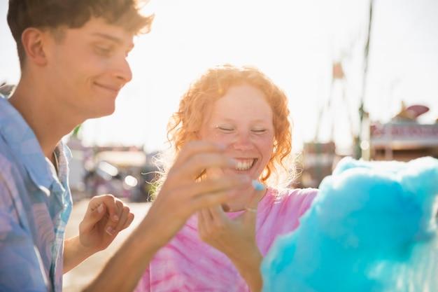Zwei spielende freunde beim essen der zuckerwatte Kostenlose Fotos