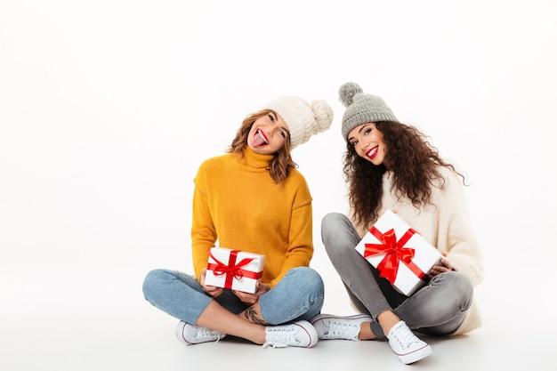 Zwei spielerische mädchen in den strickjacken und in hüten, die zusammen mit geschenken auf dem boden über weißer wand sitzen Kostenlose Fotos