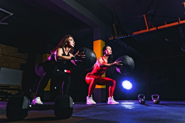 Zwei sportfrauen, die hockenübungen mit eignungsball tun. frau, die mit medizinball an der turnhalle trainiert und ausdehnt Premium Fotos