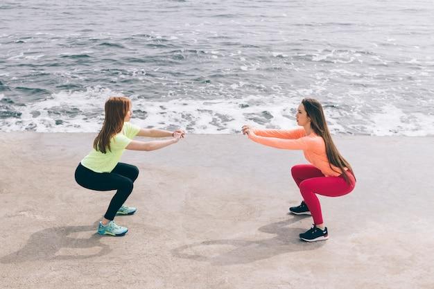 Zwei sportmädchen machen kniebeugen am strand. Premium Fotos