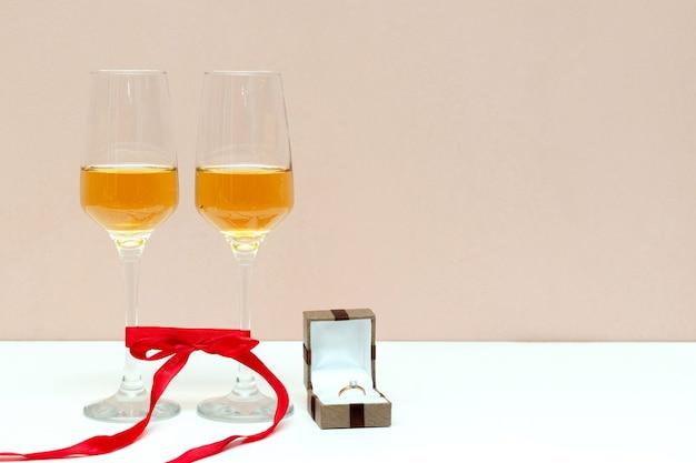 Zwei sprudelnde champagnergläser und schachtel mit goldenem ring auf weiß mit kopienraum, valentinstag, liebe, vorschlagskonzept. Premium Fotos