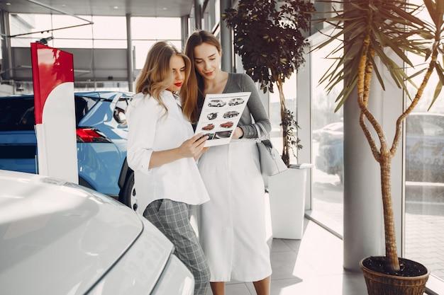 Zwei stilvolle frauen in einem autosalon Kostenlose Fotos
