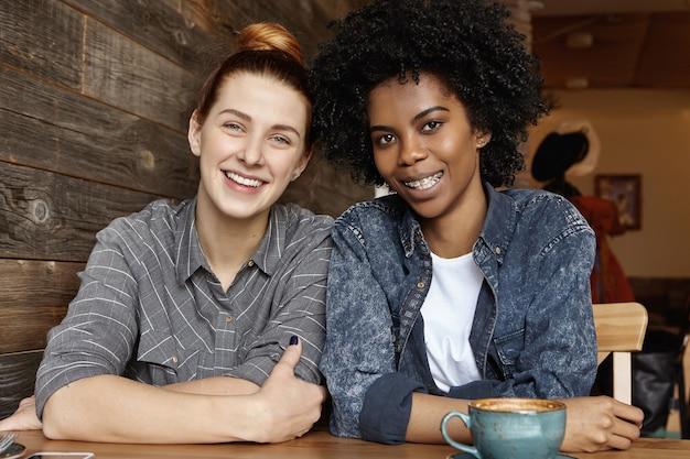 Zwei stilvolle lesben, die zusammen beim mittagessen im café kaffee trinken Kostenlose Fotos