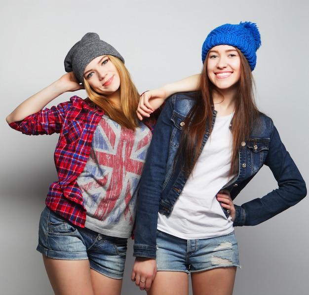 Zwei stilvolle teenager-mädchen, die mit hüten aufwerfen Premium Fotos