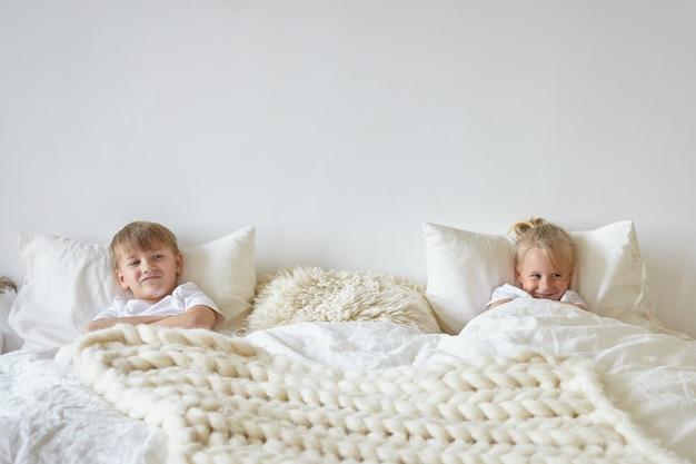 Zwei süße kinder, die sich im schlafzimmer entspannen. innenaufnahme eines jugendlichen jungen im pyjama, der mit seinem blonden kleinen bruder auf der anderen seite auf dem bett liegt und verspielte blicke hat. kindheits-, kinder- und familienkonzept Kostenlose Fotos