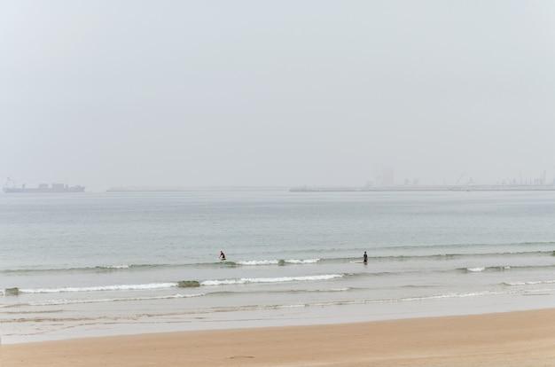 Zwei surfer, um die wellen zu reiten Premium Fotos